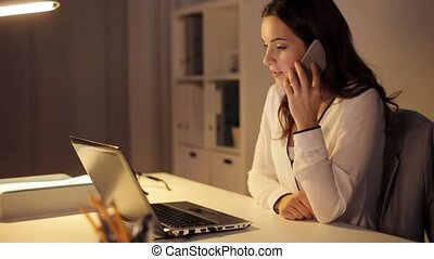woman with laptop calling on smartphone at office -...