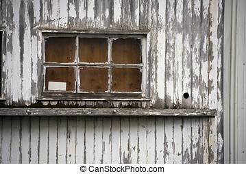 Old window of wooden house painted peeling white paint