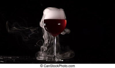 Isolated glass with wine smoke on black background. Red...