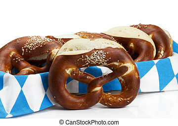 pretzel in front of pretzels in a bread basket with bavarian towel on white background