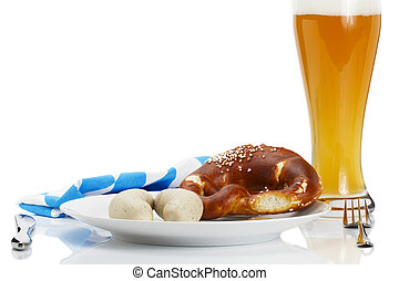bavarian veal sauages on a plate with beer, pretzel and bavarian towel on white background
