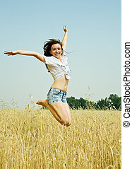 Jumping girl at field - Jumping girl at cereals field in...