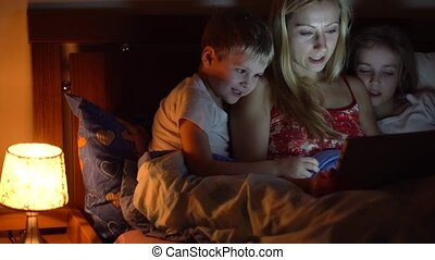mom with kids reading book in bed
