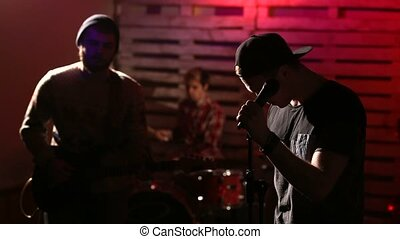 Rock band performing on illuminated stage - The scene with...
