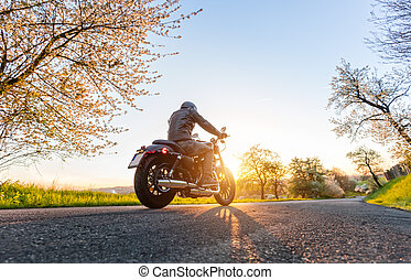 Back view of motorcycle driver on road - Back view of...