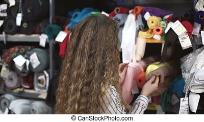 Female standing in front of shelf seller chooses the fabric.