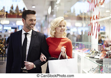 Shopping adult couple looking for sales