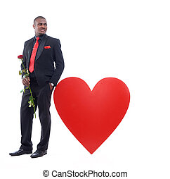 African man holding red rose, leaning on big heart. - Studio...