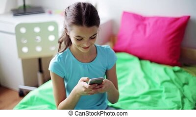 smiling girl texting on smartphone at home - children,...