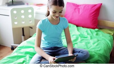 happy girl with tablet pc sitting on bed at home - people,...