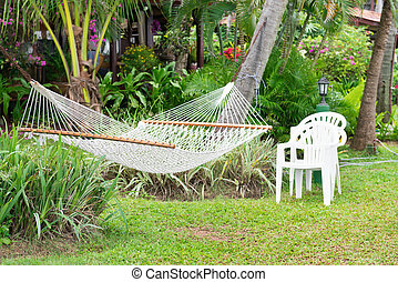 Net hammock hung on palm trees in a tropical hotel - Empty...