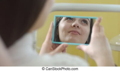 Close up portrait of young women in dentist chair. The dentist examines the mouth. Beautiful woman smiling. Through the mirror shot.