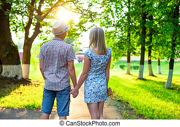 Young couple man and woman sitting on a bench hugging in park ribbon,  declaration of love,  gentle hug, concept  event  family, happy marriage. Lifestyle in the city. Outdoors.