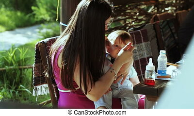 Mother feeding baby - Mom feeding baby with spoon on nature