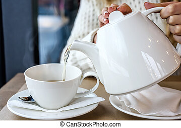 Woman pouring a Cup of hot steaming tea in the restaurant. Winter leisure, cold weather,  drink