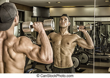 Handsome young man exercising shoulders in gym