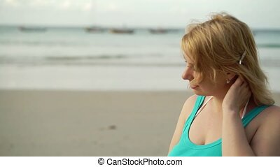 Young blonde woman on the beach in shirt and hut