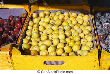 Frische Mirabellen in Holzkisten auf einem Marktstand,...