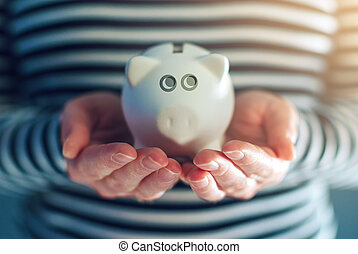 Home budget concept with piggy coin bank in female hands