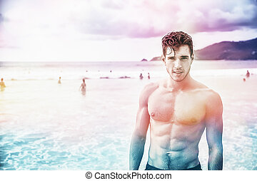 Young man standing on edge of the ocean - Heavily filtered...