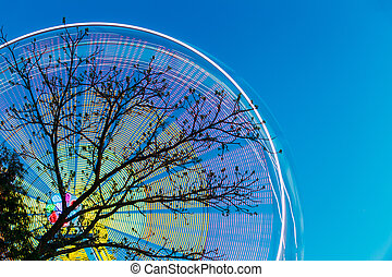 Tree Branches Against Backdrop Of Bright Spinning Ferris...
