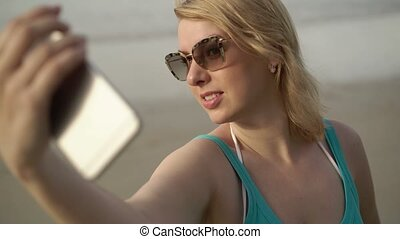 Young blonde woman on the beach taking selfie photo