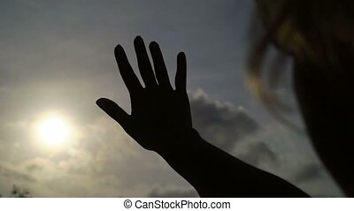 Woman catching the sun by hand silhouette