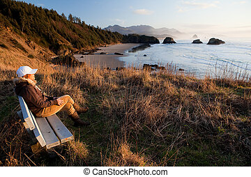 woman enjoying view at Oregon Coast - woman sitting on a...