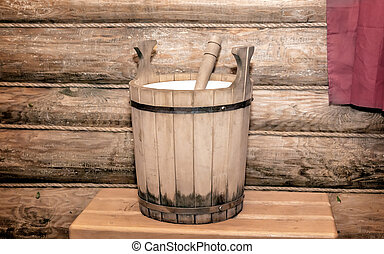 Barrel for water in a wooden sauna. - The interior of a...