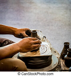 Hands shaping clay pot