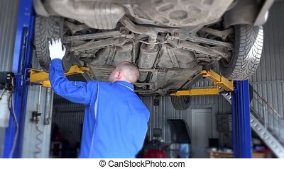 mechanic examining automobile lifted in garage. - Mechanic,...