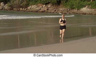 Woman jogging on a beach - Young woman jogging on a beach in...