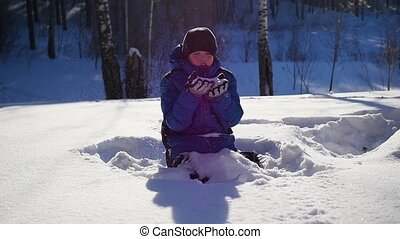teen blows snow with hands in closeup