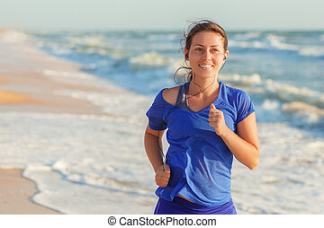 Fitness girl running on the beach