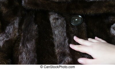 detail of a mink coat - Women's hand gently holds along the...