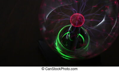Colorful plasma ball is on the table and illuminates during...