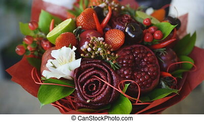 Woman rotating bouquet of fruits: lime, strawberry, pomegranate, marshmallow, apple
