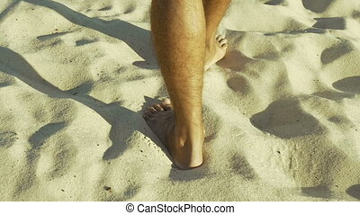 Male feet walking on sand. Tanned man in khaki shorts...