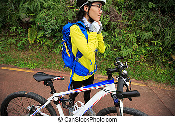 young woman cyclist put on bike helmet before riding