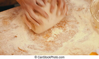 Female hands kneading dough in flour on table - Women's...