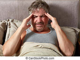Sick man in bed - Sick man with flu and headache lying in...