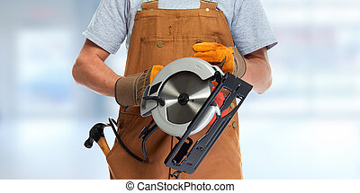 worker hands with electric saw - professional construction...