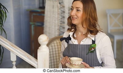 young cook chef woman talks and drink tea with her...