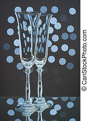 Two empty champagne glasses on blue background