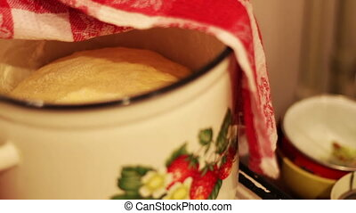 Raw dough in the pan is covered with a red table cloth on...