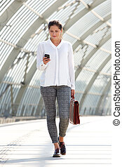 young business woman walking with bag and mobile phone -...
