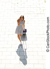 young happy woman talking on mobile pulling suitcase -...
