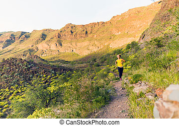 Young woman running on mountain trail at sunset