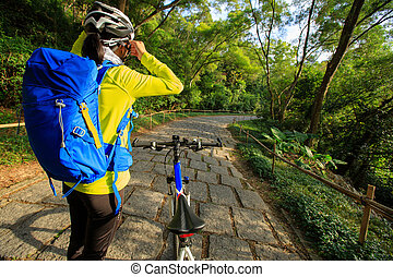 young woman cyclist adjust the helmet belt before riding...