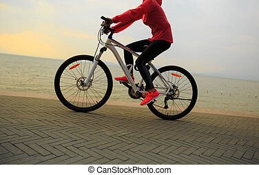 healthy lifestyle young woman riding bike on seaside